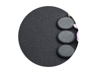 Flat lay composition with stones and orchid flowers on black sand, space for text. Zen concept