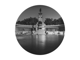 Monochrome long exposure of people on boats across from monument to Alfonso XII in the Parque del Buen Retiro, known as the Park of the Pleasant Retreat in Madrid, Spain