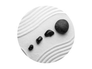Black stones on sand with pattern, top view. Zen, meditation, harmony